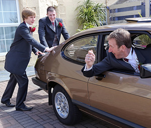 Ushers pushing Groom in brown car