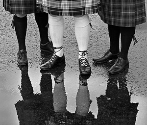 Reflection of wedding party in a puddle